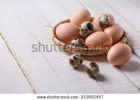 Chicken and quail eggs on white wooden background. Selective focus. - stock photo