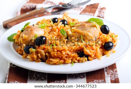 Chicken and rice casserole in sauce with black olives - stock photo