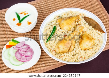 Chicken Biryani Top View - Overhead view from the top of delicious Indian chicken biryani with garnish, served with raita and colorful salad. Traditional presentation. - stock photo