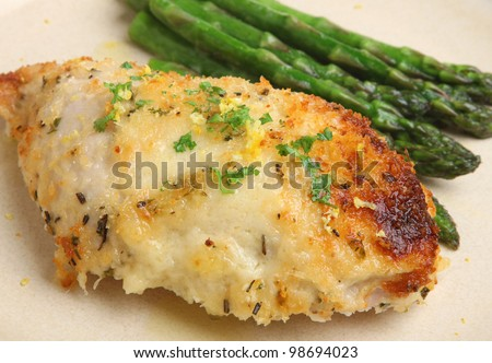 Chicken breast fillet baked with Parmesan cheese, lemon and herbs - stock photo