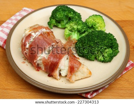 Chicken breast stuffed with cheese sauce and wrapped in pancetta. - stock photo