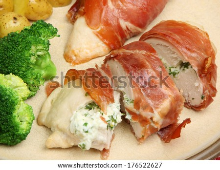 Chicken breast stuffed with cottage cheese and herbs and wrapped in pancetta. - stock photo