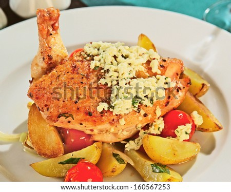 Chicken breast with roasted potatoes, grated cheese and tomatoes - stock photo