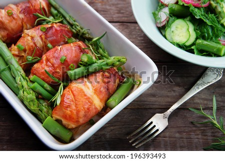 chicken breast wrapped in parma ham with green asparagus inn ceramic dish - stock photo