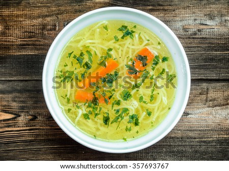 Chicken broth soup with noodles on a wooden table. - stock photo