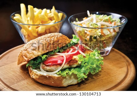 Chicken burger. Chicken filet, tomatoes, green salad, onion with Mayonnaise sauce and french fries - stock photo