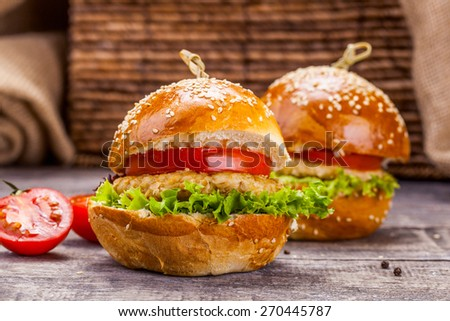 Chicken burgers on wooden table - stock photo