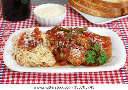 Chicken cacciatore stew with spaghetti on the side and a side of Italian bread. - stock photo