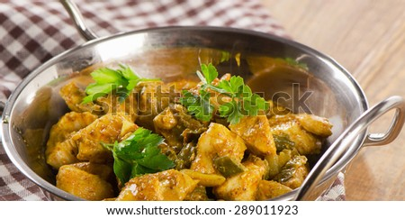 Chicken curry in a balti dish on a wooden table. Selective focus - stock photo