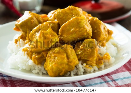 Chicken curry with rice white plate on wooden table - stock photo