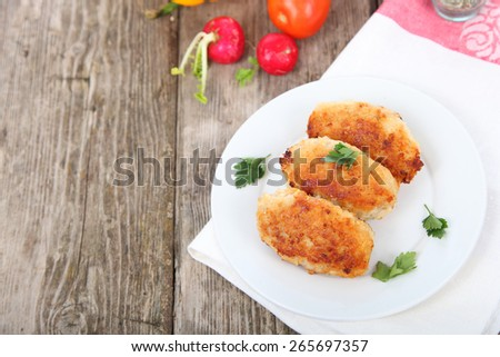 Chicken cutlets  on plate on a wooden table . - stock photo