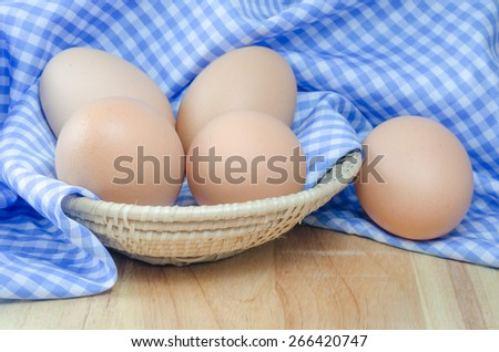 Chicken egg in a basket with blue cloth on wodden table - stock photo