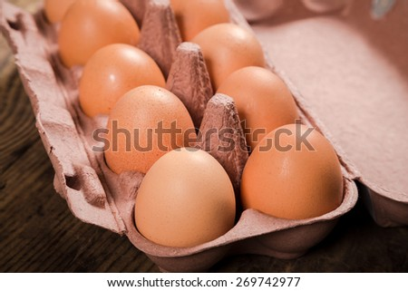 Chicken eggs in recyclable carton tray on wooden table - stock photo