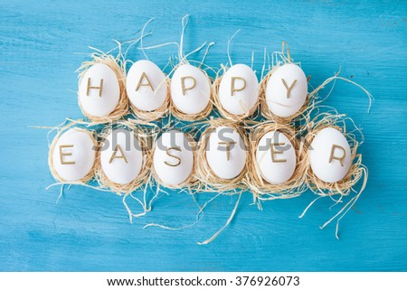Chicken eggs with easter greeting on blue wooden background - stock photo