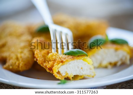 chicken fried in batter with basil on a plate - stock photo
