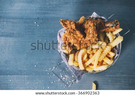 Chicken fries strips and legs with French fries in metal basket over blue wooden table with sea salt. Top view. With retro filter effect - stock photo