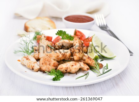 Chicken grill meat with vegetables on white plate - stock photo