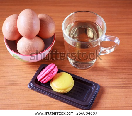 Chicken Hen Eggs in cup whit cookies and glass of drinking water on Wood table.vintage look.Chicken Hen Eggs in cup whit cookies and glass of drinking water on Wood table.vintage look.  - stock photo