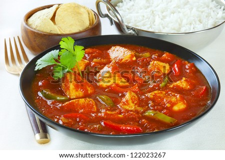 Chicken Jalfrezi with rice and poppadums. This curry was invented by Indian chefs in the time of the Raj, when left over roast chicken would have been combined with spices and vegetables. - stock photo