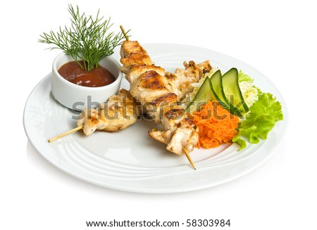 Chicken kebab with tomato sauce and vegetable side dish. - stock photo
