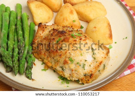 Chicken kiev, stuffed with garlic and herb butter, with asparagus and roast potatoes. - stock photo
