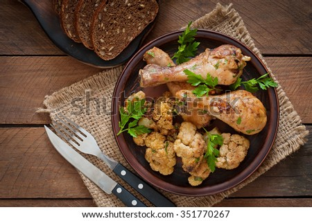 Chicken leg with baked cauliflower and parsley. Top view - stock photo