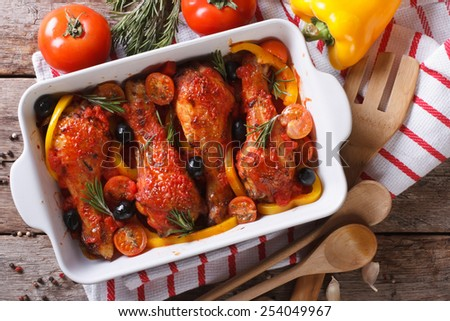 Chicken legs baked in tomato sauce with olives close-up. horizontal view from above
