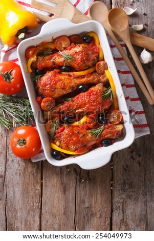 Chicken legs baked in tomato sauce with vegetables. vertical view from above close-up