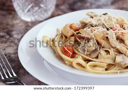 Chicken linguine with grilled chicken, tomatoes, mushrooms and freshly grated parmesan cheese. - stock photo