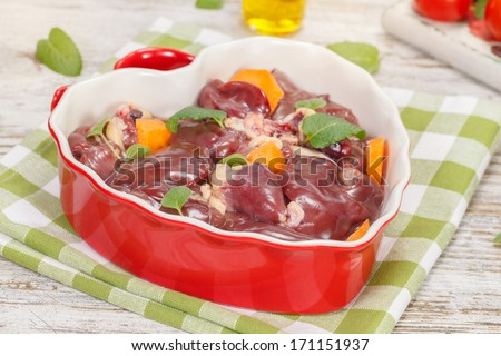 Chicken liver. Raw chicken liver in heart shaped bowl. Macro, close up - stock photo