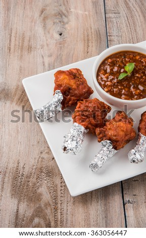 chicken lolipop, chicken winglet, tandoori chicken. Famous indian non veg dish, roasted chicken covered with silver foil, served with spicy chutney, indian chinese appetizer - stock photo