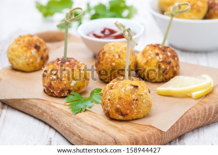 chicken meatballs in corn breading with tomato sauce on a wooden board, close-up - stock photo