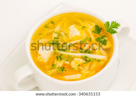 Chicken noodle soup in white mug on white background - stock photo