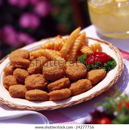 Chicken nuggets and french fries in outdoor setting. - stock photo