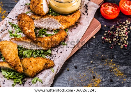 chicken nuggets, breaded posted on Boards with tomatoes and spices - stock photo
