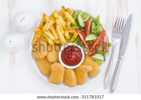 chicken nuggets, french fries and vegetable salad, top view, horizontal - stock photo