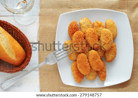 chicken nuggets served in a white bowl on a white wooden table of a rustic kitchen - stock photo