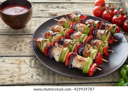 Chicken or turkey meat shish kebab skewerrs with onion tomatoes and ketchup in clay dish on rustic wooden background. Traditional barbecue grill food - stock photo