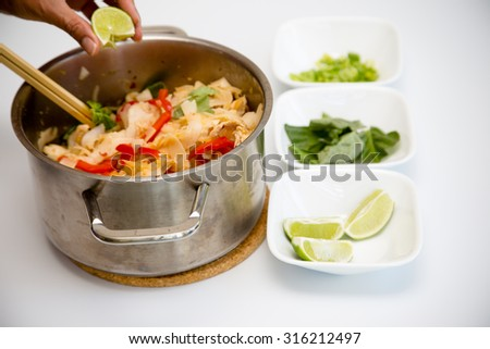 Chicken Pad Kee Mao with Bell Pepper and Thai Basil with side garnish of Thai basil, lime, and scallions - stock photo
