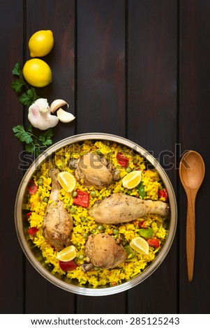 Chicken paella, a traditional Valencian (Spanish) rice dish made of rice, chicken, peas, capsicum and served with lemon in pot, photographed on dark wood with natural light - stock photo