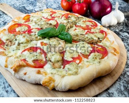 Chicken Pesto and Tomato Pizza: A whole gourmet chicken pesto pizza with fresh tomatoes and basil - stock photo