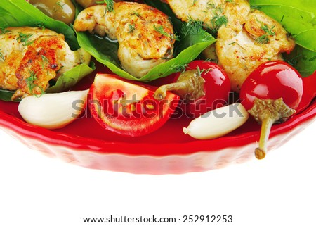 chicken pieces on red dish with tomatoes - stock photo