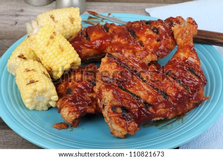 Chicken quarters and corn on the cob on a platter - stock photo