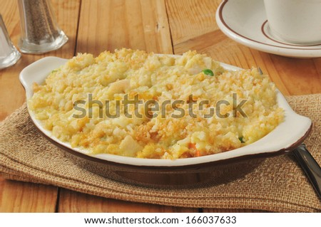 chicken rice casserole with vegetables on a rustic wooden table - stock photo
