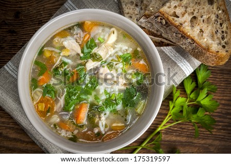 Chicken rice soup with vegetables in bowl and bread from above - stock photo