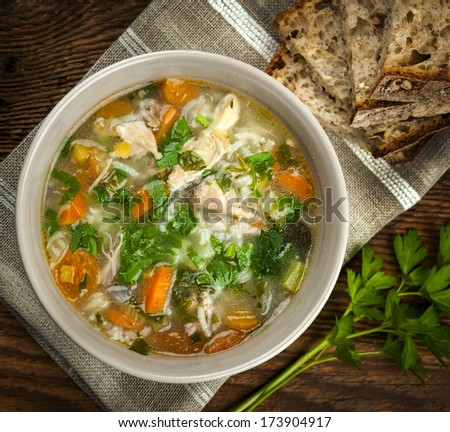 Chicken rice soup with vegetables in bowl and bread from above closeup - stock photo