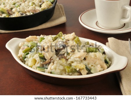 Chicken risotto with asparagus and mushrooms in a mini casserole dish - stock photo
