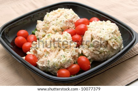 Chicken salad scoops arranged in small black bowl with grape tomatoes - stock photo