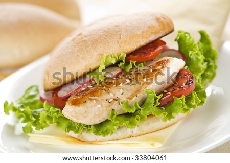 Chicken sandwich with salad and tomato close up - stock photo