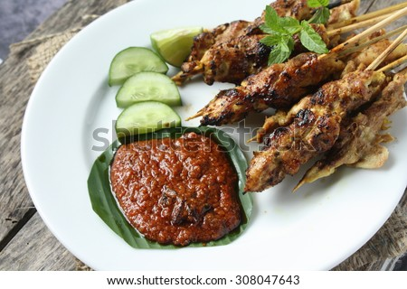 Chicken Satay or Sate Ayam - Malaysian famous food. Satay, modern Indonesian and Malay spelling of sate, is a dish of seasoned, skewered and grilled meat, served with a peanut sauce - stock photo